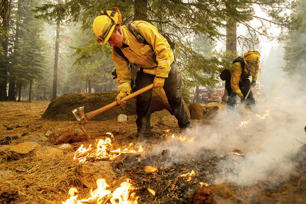 Firefighters Erik Padilla (left) and Joe Young extinguish hot spots last week while protecting Lake Almanor West homes from the Dixie Fire in California's Plumas County.