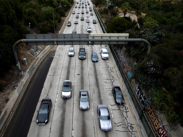 Cars drive down the 110 Freeway toward downtown Los Angeles, California in April 2021. President Biden has pledged to cut U.S. greenhouse gas emissions in half by 2030.