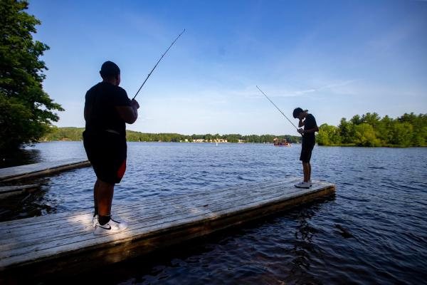 Chaun'cee Smith and Josiah Lopez fish off a dock in Lake Lashaway at Camp Atwater in North Brookfield. (Jesse Costa/WBUR)