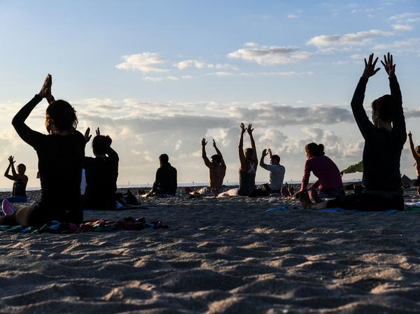 People do yoga on the beach in Miami Beach, Fla., on March 23.