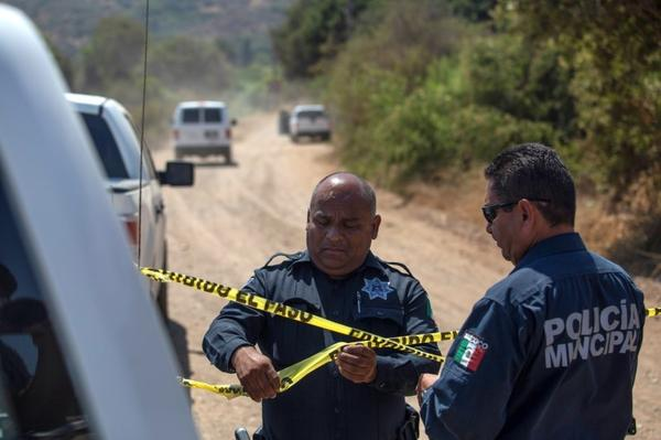 Officers hold a police cordon at the scene where two young American children were found dead in Rosarito in the Mexican state of Baja California on Monday.