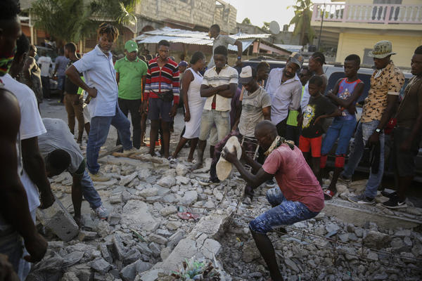 A man digs with a stone through the rubble of a house destroyed by the earthquake in Les Cayes, Haiti, on Sunday.