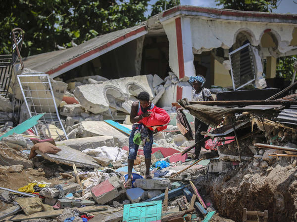 Locals recover their belongings Sunday from their homes destroyed in the earthquake in Camp-Perrin in Les Cayes, Haiti.