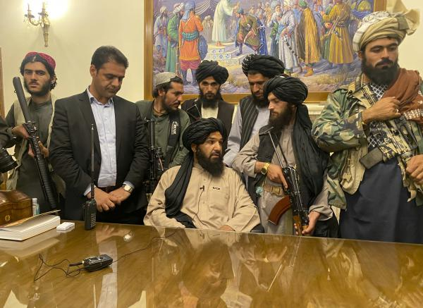 Taliban fighters take control of Afghan presidential palace in Kabul on Sunday, after President Ashraf Ghani fled the country. The person second from left is a former bodyguard for Ghani.