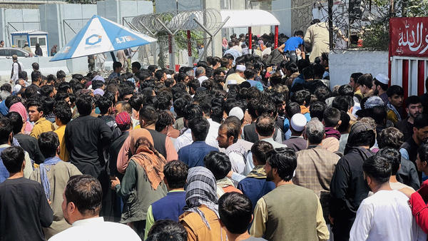 Afghans rush to the Hamid Karzai International Airport as they try to flee the Taliban takeover of Kabul.