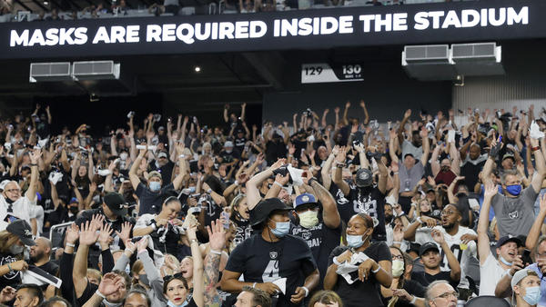 Raiders fans do the wave during last weekend's preseason game in Las Vegas as a stadium sign reminds them to wear face masks. The team now says spectators will have to show proof of vaccination — and that no masks will be required for those who have been vaccinated.