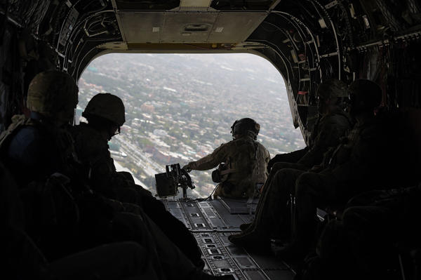 In this photograph taken on Aug. 10, 2017, a U.S. soldier sits in the rear of Chinook helicopter while flying over Kabul.