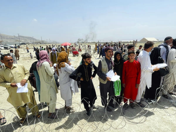 Hundreds of people gather outside the international airport in Kabul, Afghanistan, on Tuesday.
