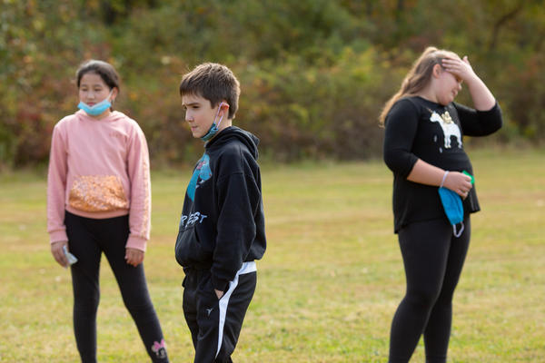 A group of fifth-grade students remove their masks during an outdoor mask break.