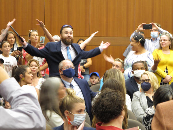 Angry, largely unmasked people objecting to Louisiana Gov. John Bel Edwards' mask mandate for schools shout in opposition to wearing a face covering at the Board of Elementary and Secondary Education meeting on Wednesday in Baton Rouge, La.