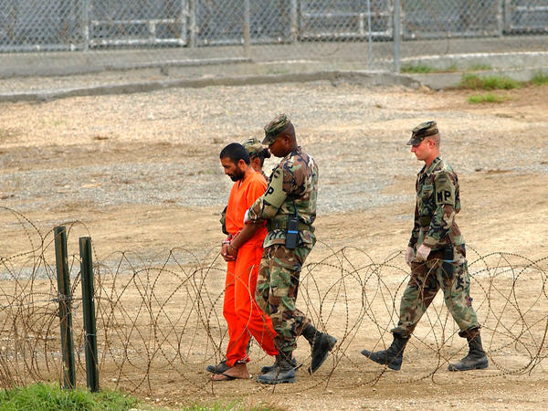 Marines transport a detainee in Guantánamo Bay, Cuba, in 2002. Nearly 800 detainees have passed through the prison since it opened that year. Today, 39 men are still being held there.