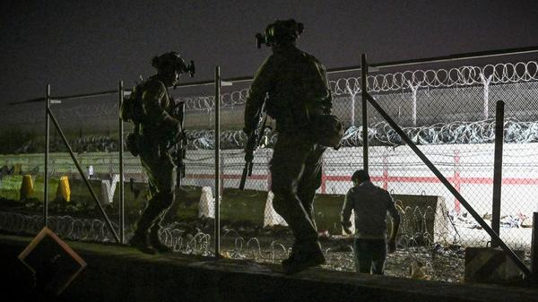 British and Canadian soldiers stand guard late Sunday near a canal as Afghans wait outside the foreign military-controlled part of the airport in Kabul, hoping to flee the country following the Taliban's military takeover of Afghanistan.