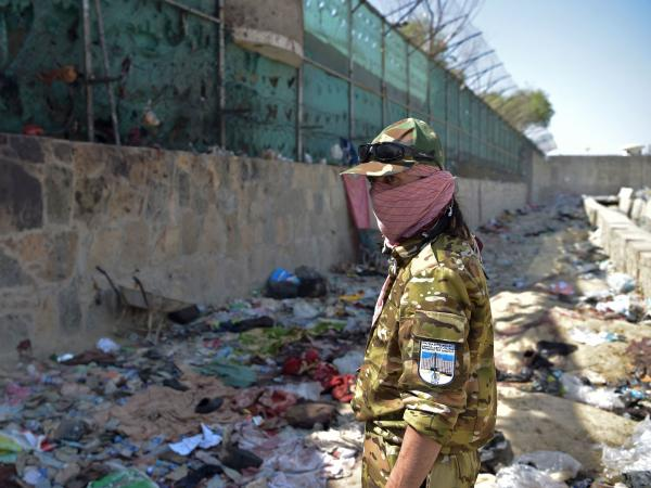 A Taliban fighter stands guard Friday at the site of the bombing that killed scores of people, including 13 U.S. troops, near the airport in Kabul. The U.S. is blaming ISIS-K for Thursday's attack.