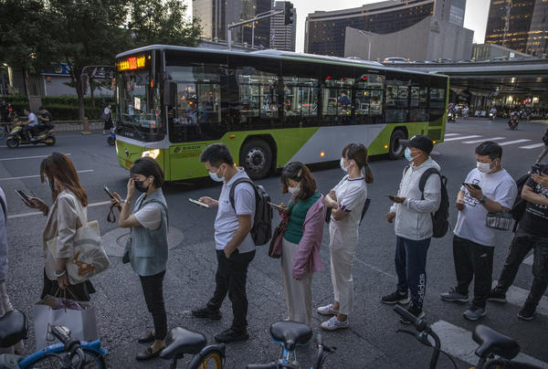 """Commuters wait in line for public buses as they leave work in Beijing's business district on Aug. 27. China's Supreme People's Court has ruled that it's illegal for companies to subject employees to the practice known as """"996,"""" or working 9 a.m. to 9 p.m. six days a week."""
