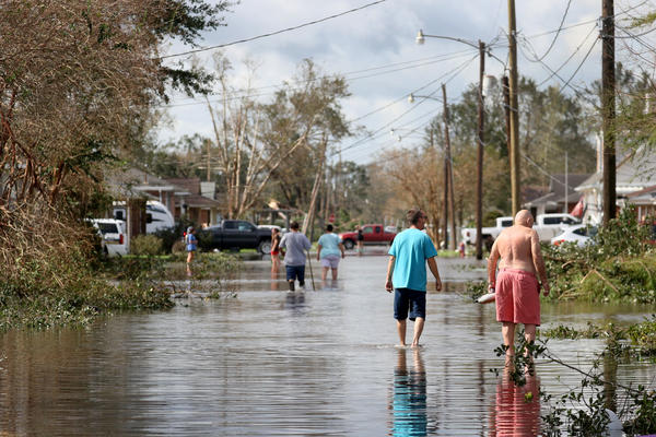 Residents walk down a flooded residential street in the aftermath of Hurricane Ida on Monday in Norco, La. Ida made landfall on Sunday as a Category 4 storm southwest of New Orleans.