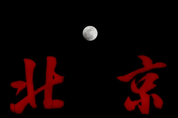 """The super blue blood moon rises over Chinese signs reading """"Beijing"""" atop a building in Beijing."""