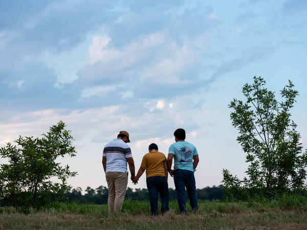 Honduran migrants, Ricardo Sr., (left), his son Ricardo Jr., 13, and his cousin Jorge, 16, walk near their home in Texas. When the two teenage boys crossed the border illegally into Texas last month, they turned themselves in to the Border Patrol. They were later escorted to a hotel by armed men in civilian clothes.
