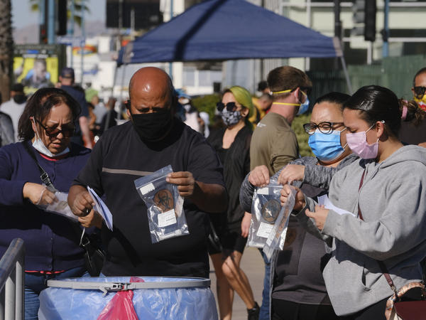 People drop their test kits into a receptacle at a coronavirus testing site in the North Hollywood section of Los Angeles on Saturday. With COVID-19 cases surging at a record pace in California, Gov. Gavin Newsom has warned that the state's hospitals could soon be overwhelmed.