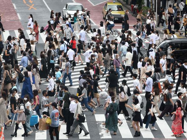 Pedestrians cross the landmark Shibuya Crossing intersection in the shopping and entertainment district of Shibuya in Tokyo on June 27, 2021.