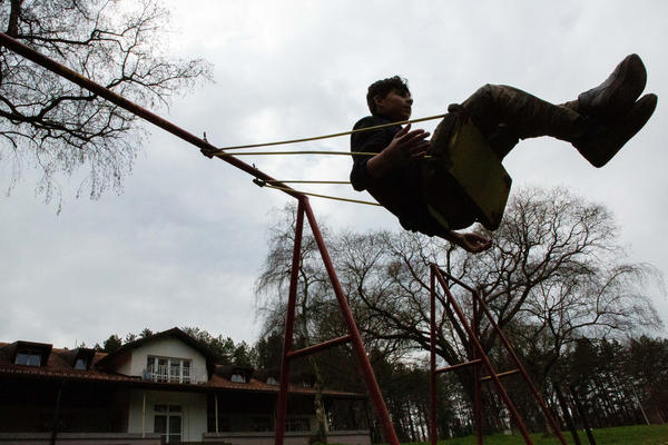 """Mohammad Bilal, 17, from Afghanistan, plays on a swing at Bogovadja asylum center in central Serbia. He reached Serbia alone after smugglers in Iran put him in the trunk of a car alongside four other children with no water and amid scorching temperatures. """"I thought that was my last day on earth,"""" he says."""