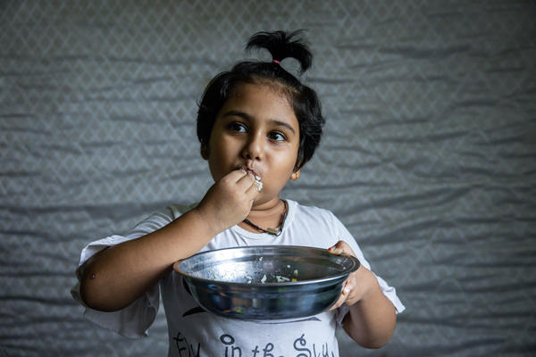 Hosna Ali, 6, eats rice with dried fish at home in Seleyang, Malaysia. Her dad, Mohd Ali, says the family has not been getting enough nutrients during the pandemic.
