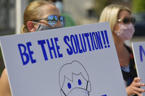 Demonstrators calling on people to wear masks gather outside school district headquarters in Marietta, Ga., last week. A recent review at pandemic data finds requiring masks, capping the size of gatherings and instituting certain bar, gym and restaurant restrictions are all strategies that can help stop a surge in COVID-19 hospitalizations.