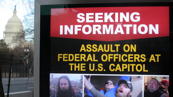 An information board shows people who are wanted by law enforcement on suspicion of assaulting federal officers at the U.S. Capitol during the Jan. 6 riot.