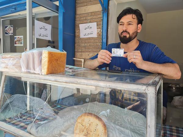 Afghan refugee Mohammed Reza Zafar, 35, displays his U.N. refugee card at an Afghan bakery where he works in India's capital of New Delhi.