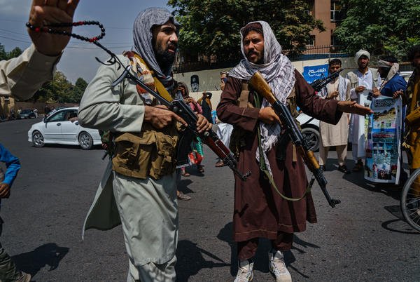 Taliban fighters mobilize to control a crowd during a rally for Afghanistan's independence day in Kabul on Aug. 19. The Taliban seized control of the city this week, effectively capturing the country in a matter of weeks.