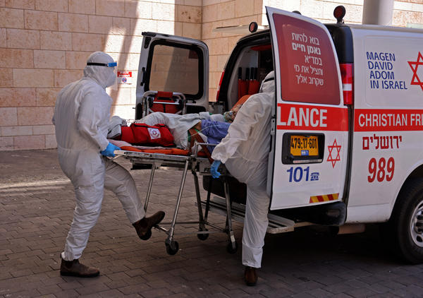 Medics in Jerusalem transfer a COVID-19 patient to Hadassah Hospital Ein Kerem. Many hospitals in Israel are at full capacity following a sharp increase in coronavirus infections.