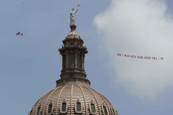 A plane pulls the message 'Don't Mess with Texas Voter Y'all' over the Texas Capitol on July 13 in Austin, Texas. Democrats left the state to block sweeping new election laws and began to return this week.