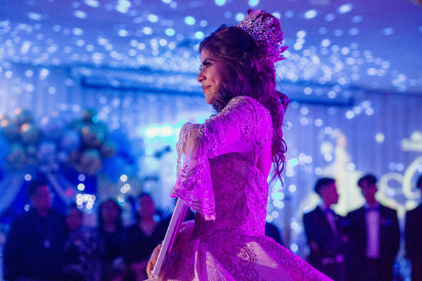 Citlaly Olvera Salazar dances with an image of her grandfather, Antonio Salazar, and father, Cesar Olvera, in their absence during her Quinceañera.