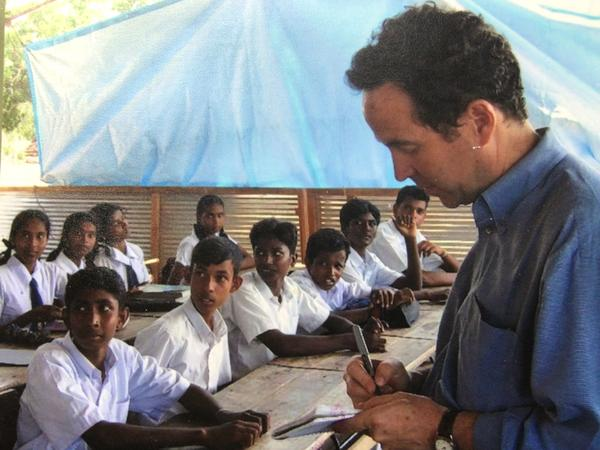 """Joel Charny, who's been a humanitarian aid worker for 40 years, talks to students at a camp for internally displaced people in northern Sri Lanka in 2005. It's one of his favorite photos, he says, """"because this is what I did hundreds of times: interview people about what they were going through and what they needed for their lives to improve."""""""