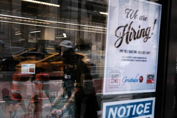 A hiring sign gets displayed in a store window in New York City in August. Last month saw a sharp slowdown in hiring from previous months as the pandemic wears on and creates uncertainty.