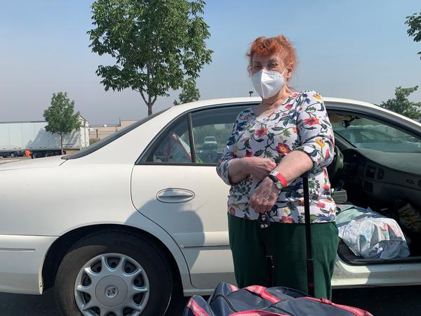 Mimi Routh, 79, unloads a suitcase from her car after evacuating from the Tahoe Senior Plaza to a shelter in nearby Gardnerville, Nev.