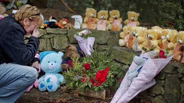 A mourner kneels beside 26 teddy bears, each representing a victim of the Sandy Hook Elementary School shooting, at a sidewalk memorial in 2012 in Newtown, Conn.