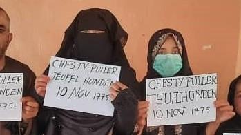 """Two family members show the signs they held so U.S. troops could spot them in the crowd at the Kabul airport. """"Chesty Puller"""" refers to a legendary U.S. Marine general. """"Teufel Hunden"""" means """"Devil Dog,"""" in German and is the name German troops used for Marines in World War I. <strong>""""</strong>10 Nov., 1775,"""" is the day the Marines were founded. All eight family members made it to safety."""