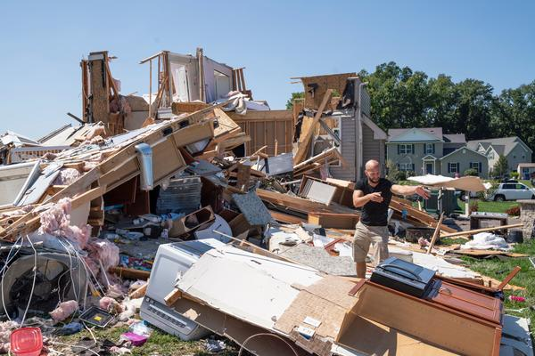 Sam Catrambone clears debris away from a friend's home that was damaged by a tornado in Mullica Hill, N.J., on Thursday after record-breaking rainfall brought by the remnants of Hurricane Ida that swept through the area.