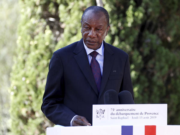 Witnesses say heavy gunfire has erupted near the presidential palace in Guinea's capital and went on for hours. It was not immediately known whether President Alpha Conde, seen above in August 2019, was home at the time the shooting began.