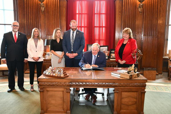 Flanked by state lawmakers, Gov. Mike Parson signs House Bill 604 into law on July 7, 2021.