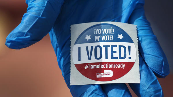"""A voter holds an """"I Voted!"""" sticker after casting her ballot during the Florida presidential primary last March."""