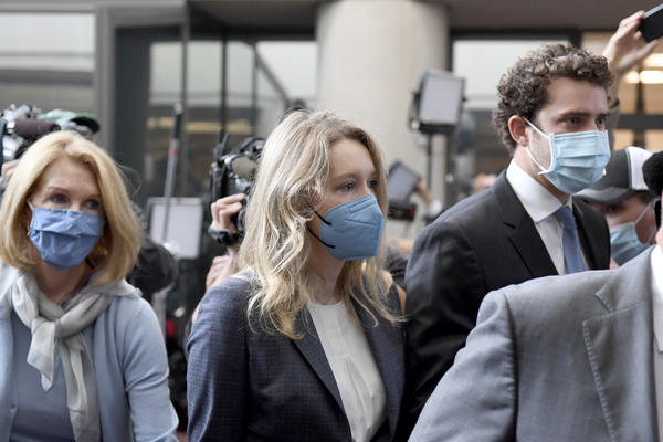 Elizabeth Holmes (center) walks into the federal courthouse for her trial in San Jose, Calif., on Wednesday.