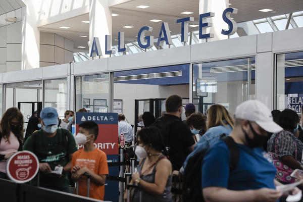 Travelers wearing protective face masks wait in line at a Transportation Security Administration screening at LaGuardia Airport in New York last month. U.S. aviation regulators are calling on the nation's airports to crack down on the defiantly unmasked.