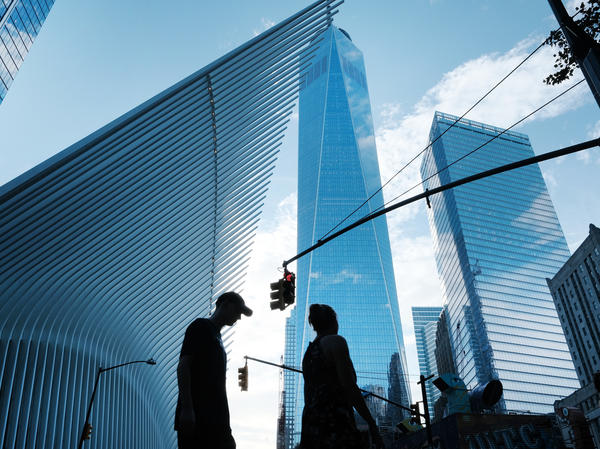 People walk near the sight of Ground Zero and the One World Trade Center on Aug. 30. The Wall Street neighborhood changed drastically after the 9/11 attacks as banks moved out of what had long been their home.