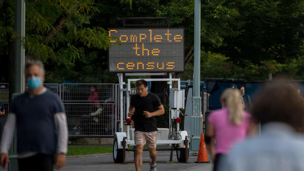 """People pass by a """"Complete the census"""" sign along New York City's Hudson River Greenway in September 2020."""
