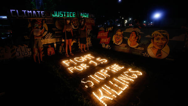 Climate activists in Quezon City, Philippines, light candles and hold LED-illuminated banners in December of last year to commemorates five years since the Paris Agreement and to call for an end to the killing of environmental defenders.