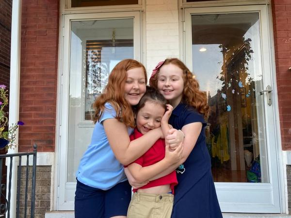 The Danieley siblings, Lucy, 10, Teddy, 5, and Ruby, 9, hug on their first day back to school on Sept. 7, 2021.