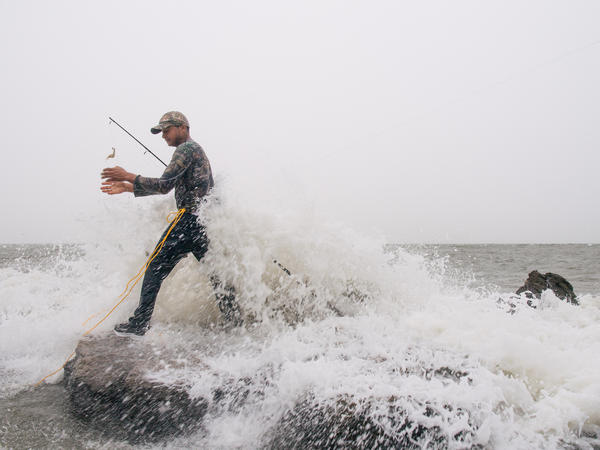 Celbing Diaz fishes ahead of Tropical Storm Nicholas in Galveston, Texas, on Monday. The storm grew overnight and made landfall as a hurricane early Tuesday.