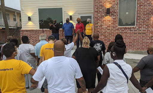 Pastor Gregory Manning leads a prayer at a rally for Local Union President Valerie Jefferson, in red.