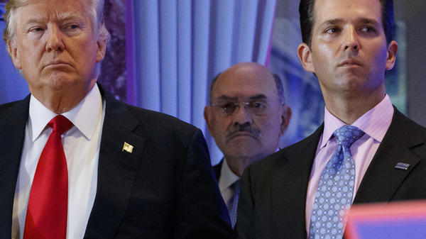 Allen Weisselberg (center), the longtime chief financial officer of former President Donald Trump's family business, stands behind Trump during a 2017 news conference at Trump Tower in New York City. Weisselberg, who appeared in court Monday, has pleaded not guilty to charges related to an alleged scheme to defraud taxpayers by paying Trump Organization executives with untaxed benefits.